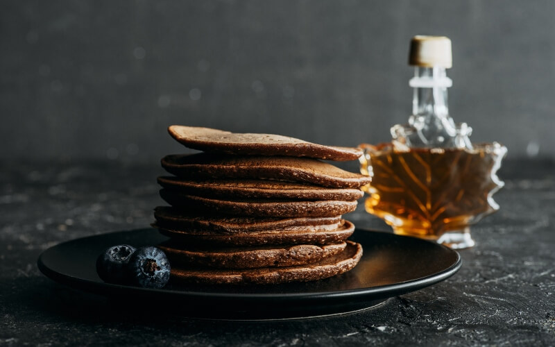 Maple syrup in a maple leaf bottle with vegan pancakes