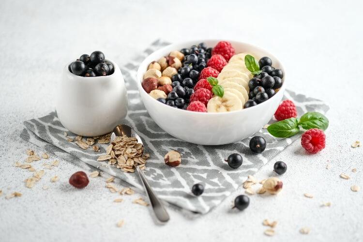 Vegan breakfast of oatmeal, bananas, nuts, and berries