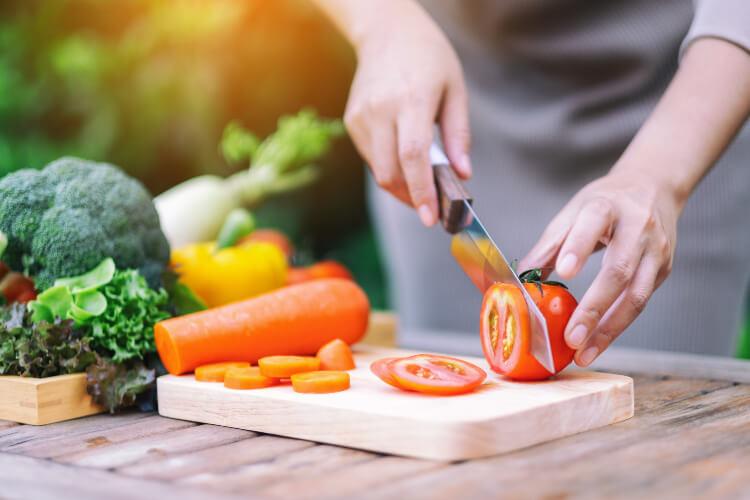 Vegan chef slicing a tomato