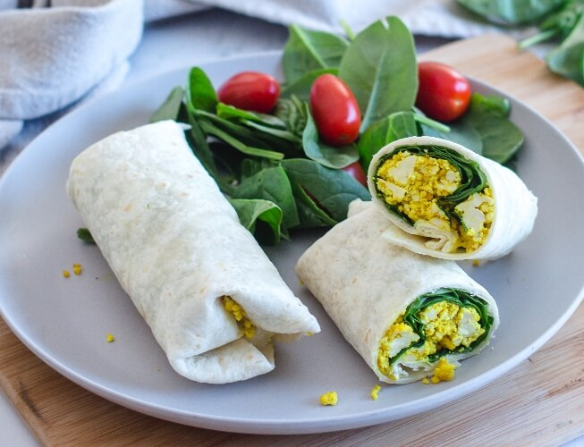 Vegan breakfast burritos with fresh spinach and cherry tomatoes
