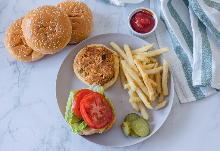 A vegan burger with fries and salad toppings
